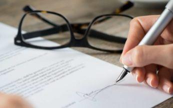 immagine di una donna che firma il proprio testamento biologico